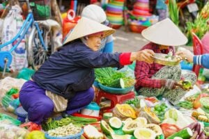 Asian woman in traditional vietnamese hats selling fresh vegetables